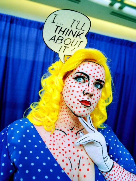 Disfraz de Halloween de comic pop art; chica con peluca amarillo canario, maquillada estilo historieta con lunares rosas y globo de diálogo