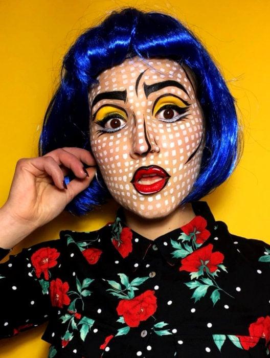 Disfraz de Halloween de comic pop art; chica con peluca color azul con corte de hongo y fleco, maquillada como historieta con lunares blancos, sombra de ojos amarilla y blusa negra con rosas rojas