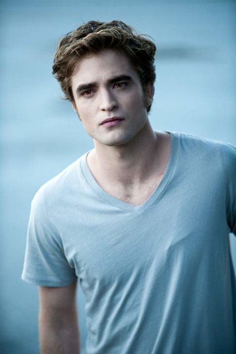 Edward Cullen usando una playera azul mientras está parado viendo a Bella