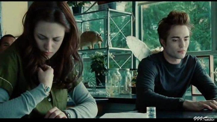 Bella oliendo su camisa mientras Edward Cullen la observa con cara de asco