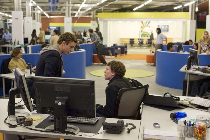 dos hombres hablan, uno sentado frente a una computadora y otro sentado en el escritorio, se ve de fondo una oficina con cubículos azules