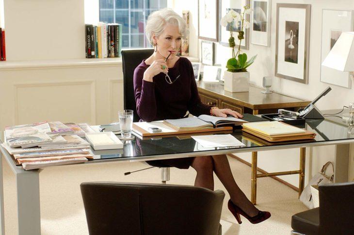 una mujer en una oficina con un escritorio de cristal con papeles encima, está pensativa con sus lentes en la mano