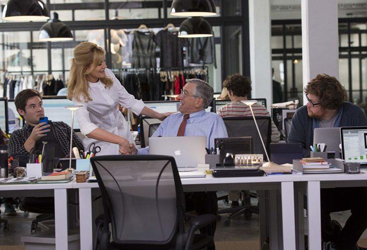 una mujer de pie habla con un hombre que está sentado en un escritorio en donde hay otros dos hombres trabajando