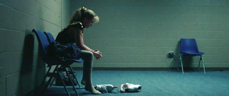 una mujer sentada en una silla en una habitación sola con sus patines tirados en el piso