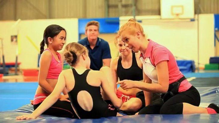 un grupo de gimnastas sentadas sobre el piso platicando