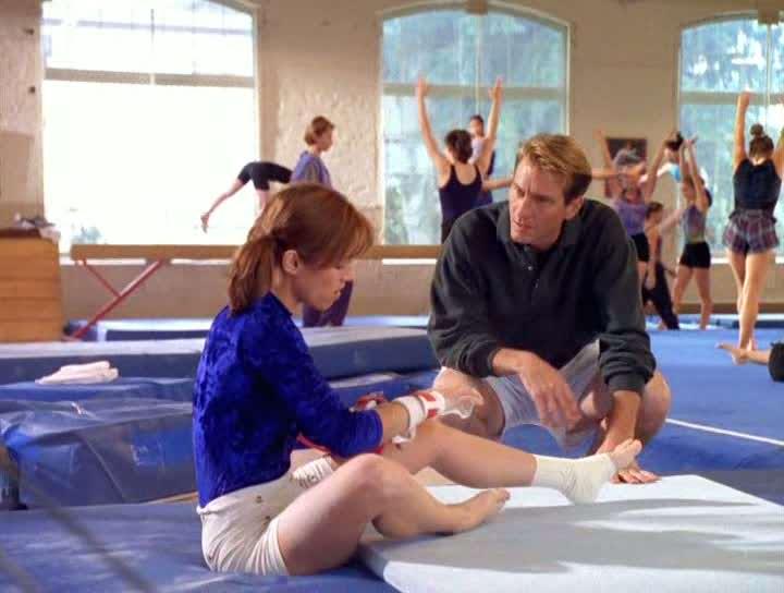 una joven sentada en el piso de un gimnasio hablando con un entrenador