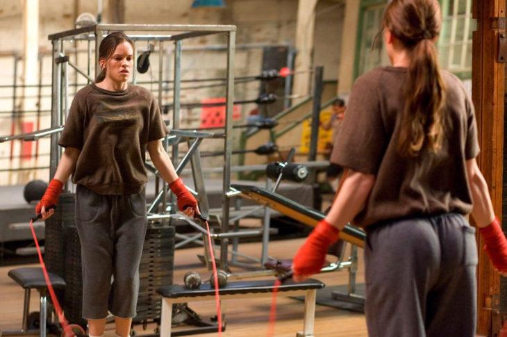 una mujer se ve en un espejo de un gimnasio saltando la cuerda