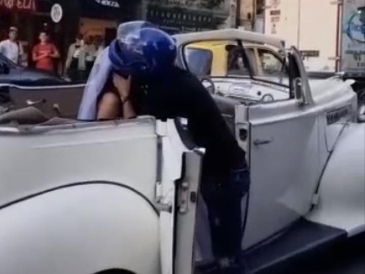 Chico con casco de motociclista besando a una chica vestida de novia dentro de un auto