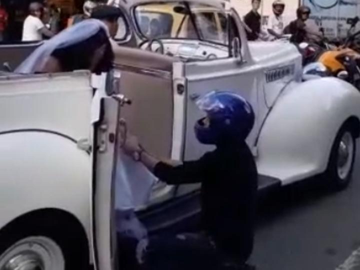 Chico arodillado frente la puerta de un auto y hablando con una chica vestida de novia