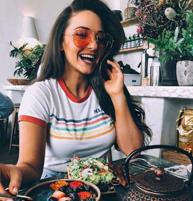 Chica sentada frente a un plato de ensalada y comiendo de manera saludable