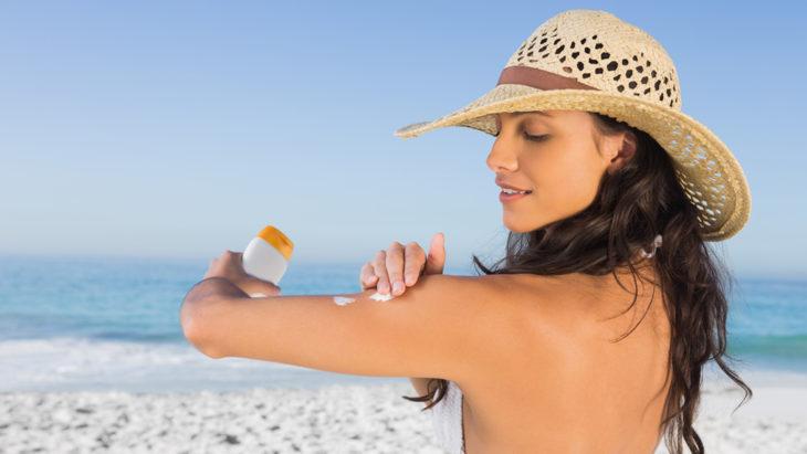 Chica untándose protector solar mientras está en la playa