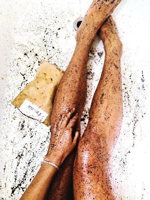 Pies de una chica cubiertos con crema exfoliante mientras ella está en la bañera