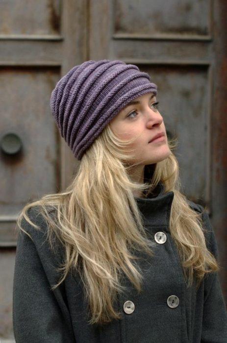 Chica llevando gorro tejido con bordos en tono morado