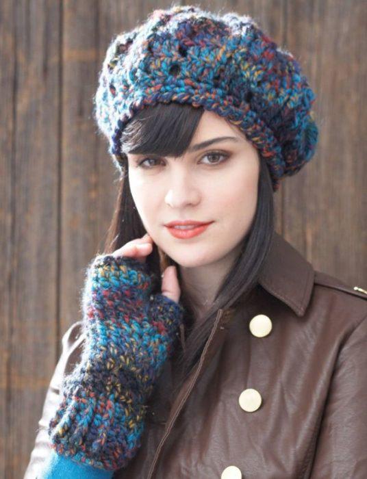 Chica con gorro tejido en forma d boina con estambre de colores