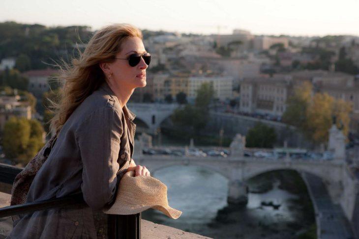 una mujer con lentes sobre un puente ve una ciudad a lo lejos