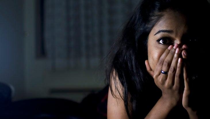 Chica recostada en la cama con rostro asustado y tapándose la cara con las manos