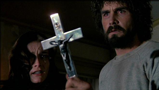 Hombre sosteniendo un crusifijo mientras su esposa está detrás de él