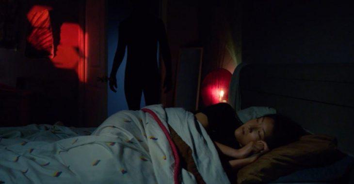 Chica dormida mientras es observada por una sombra negra que está en su cuarto