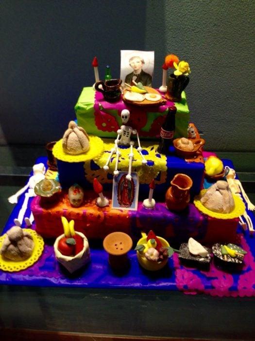 Altar de muertos decorados con papel picado, calaveritas de azúcar y catrinas de papel