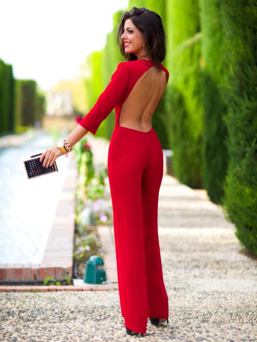 Looks con jumpsuit; mujer sonriendo frente a árboles,, con enterizo elegante color rojo de mangas 3/4 y sin espalda