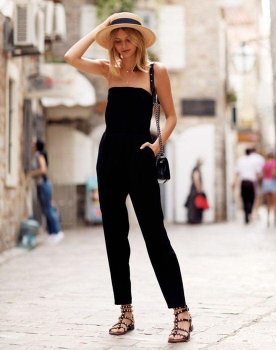 Looks con jumpsuit; chica rubia con sombrero de yute con listón, enterizo sin hombros ni mangas, color negro, con bolsa de cadena y sandalias con estoperoles
