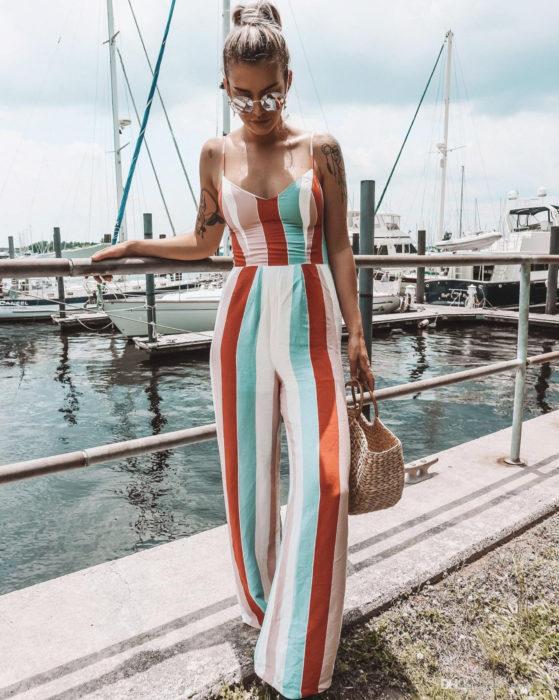 Looks con jumpsuit; chica rubia con peinado de coleta de caballo alta, en un muelle con barcos en el mar; vestida con un enterizo playero de tirantes y rayas anaranjadas, blancas,verdes y rosas verticales, bolsa de mano de yute