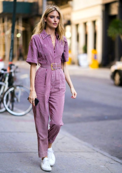 Looks con jumpsuit; chica de cabello rubio, largo y despeinado caminando en la calle con enterizo retro de botones con cinto, mangas cortas, de color morado con rayas blancas horizontales y tenis blancos