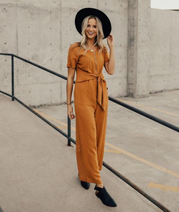 Looks con jumpsuit; chica rubia de cabello largo y ondulado con sombrero negro y enterizo con cierre color anaranjado