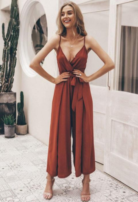 Looks con jumpsuit; muchacha posando con manos en la cintura, de cabello rubio y enterizo holgado de tirantes color café canela