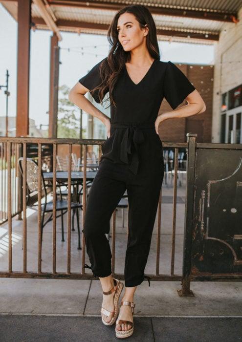 Looks con jumpsuit; chica de cabello castaño y largo, con un enterizo color negro de mangas cortas y sandalias abiertas