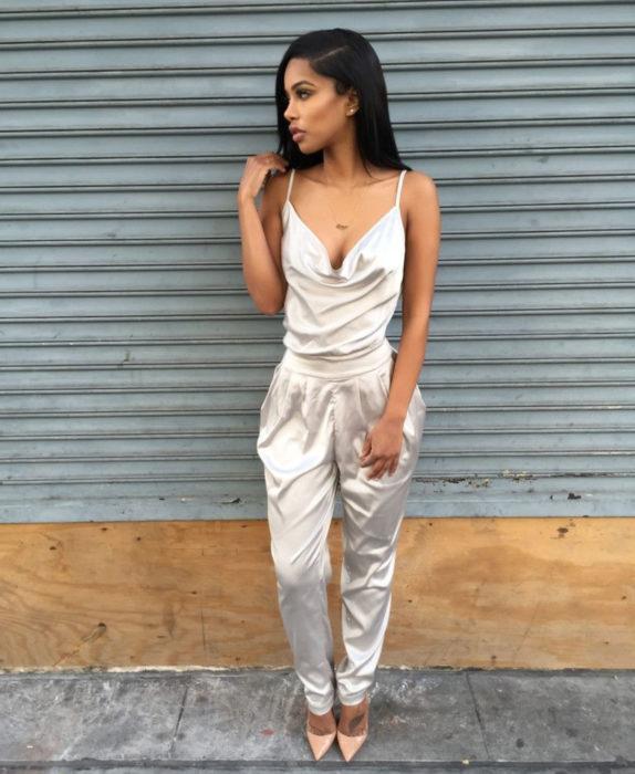 Looks con jumpsuit; mujer con cabello negro y lacio con enterizo sin mangas, color blanco perla y de tela de satín