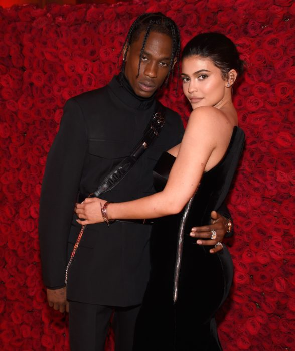 Kylie Jenner y Travis Scott se separan; pareja frente a una pared de rosas rojas