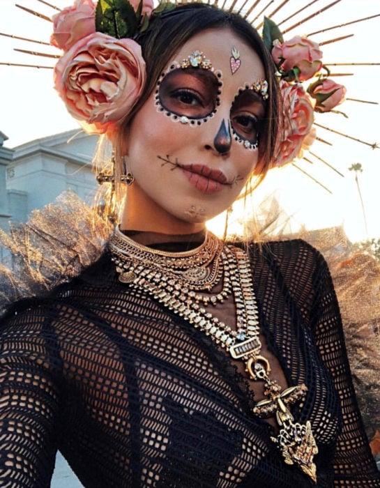 Maquillaje moderno de Catrina; chica disfrazada de Día de Muertos con flores en la cabeza, con collares y aretes de cruz dorada