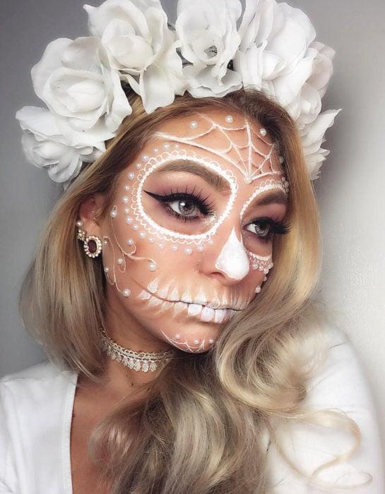 Maquillaje moderno blanco de Catrina de Día de Muertos; chica rubia con corona de rosas blancas en la cabeza