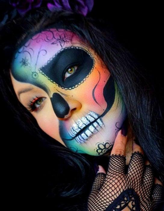 Maquillaje moderno de Catrina de Día de Muertos de colores del arcoíris, verde, azul, morado, rosa, anaranjado y rojo, con guantes de tela de red