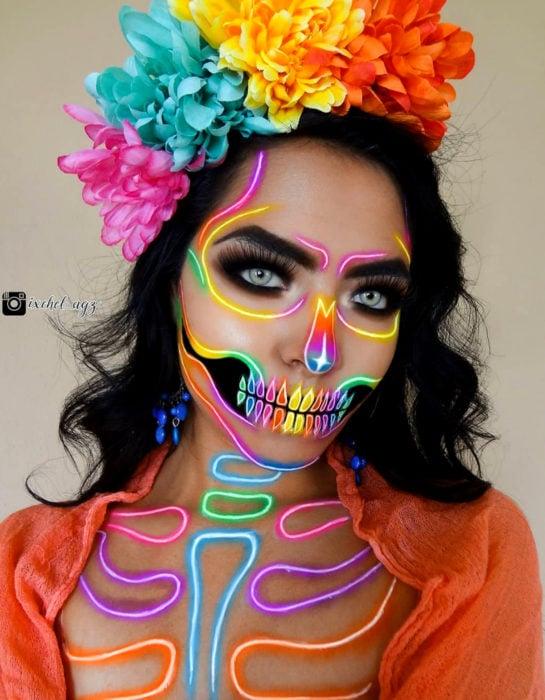 Maquillaje neón moderno de Catrina de Día de Muertos color amarillo, rosa, anaranjado, morado, azul y verde; con flores de cempasúchil en la cabeza; chica de cabello negro a los hombros y ojos verdes claro
