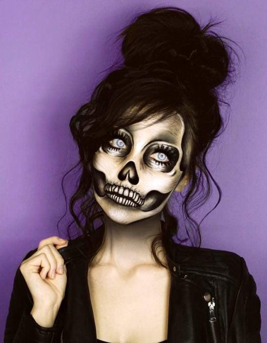 Maquillaje moderno de Catrina realista de Día de Muertos; chica de ojos azules, peinado de chongo alto y despeinado, disfrazada de calavera y chamarra de cuero