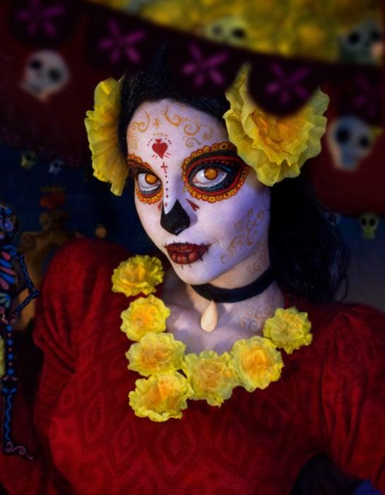 Maquillaje moderno de Catrina de Día de Muertos con flores de cempasúchil amarillas con vestido rojo; mujer disfrazada de El libro de la vida
