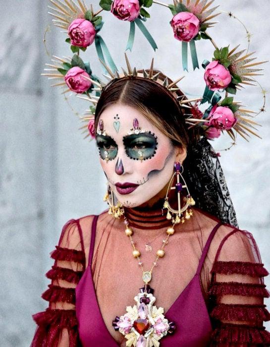 Maquillaje moderno de Catrina de Día de Muertos, con diadema dorada de picos y corona de estrellas y flores rosas, maxicollar y aretes de cruz