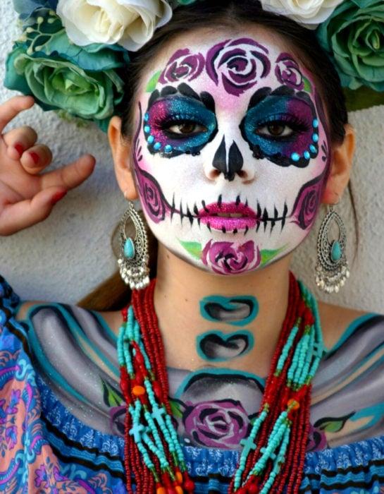 Maquillaje tradicional de Catrina de Día de Muertos de color rosa, azul y morado con glitter, corona de flores blancas y verdes y accesorios típicos