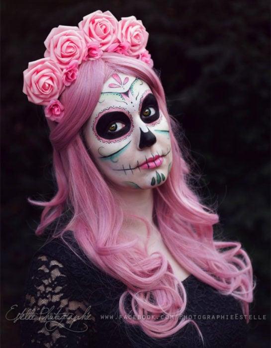 Maquillaje moderno de Catrina de Día de Muertos; chica de cabello largo, ondulado y rosa, corona de flores y blusa de encaje negro
