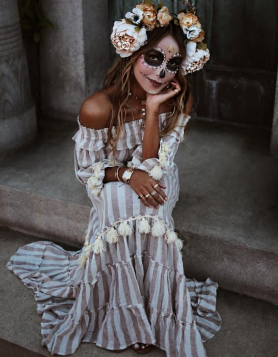 Maquillaje dorado moderno de Catrina de Día de Muertos; chica sentada en escaleras con maxivestido sin hombros de rayas verticales blancas y cafés; flores en la cabeza