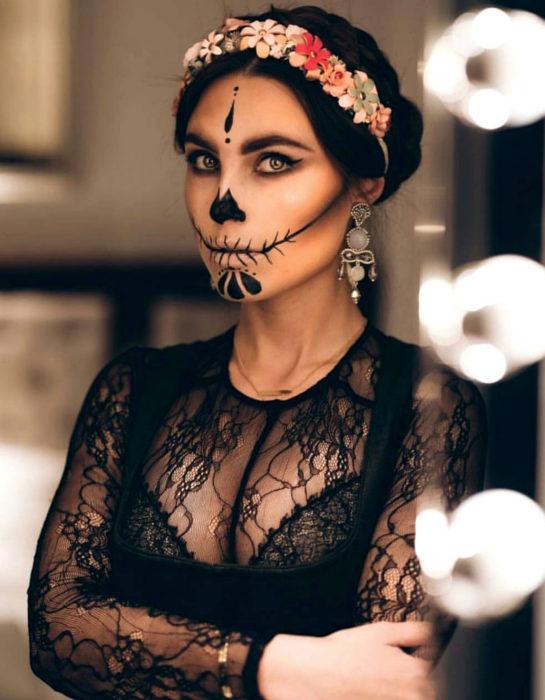 Maquillaje moderno de Catrina de Día de Muertos; mujer de ojos verdes con peinado de chongo bajo elegante, diadema de flores, aretes grandes y blusa de encaje negro
