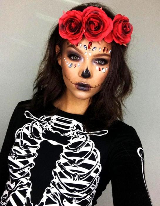 Maquillaje moderno de Catrina de Día de Muertos, sombra de ojos morada y negra, con piedras swarovski en el rostro, con blusa de estampado de calavera, corona de flores rojas