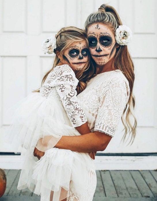 Maquillaje moderno de Catrina de Día de Muertos; madre e hija disfrazadas de calavera con vestidos blancos de encaje y flores en el cabello