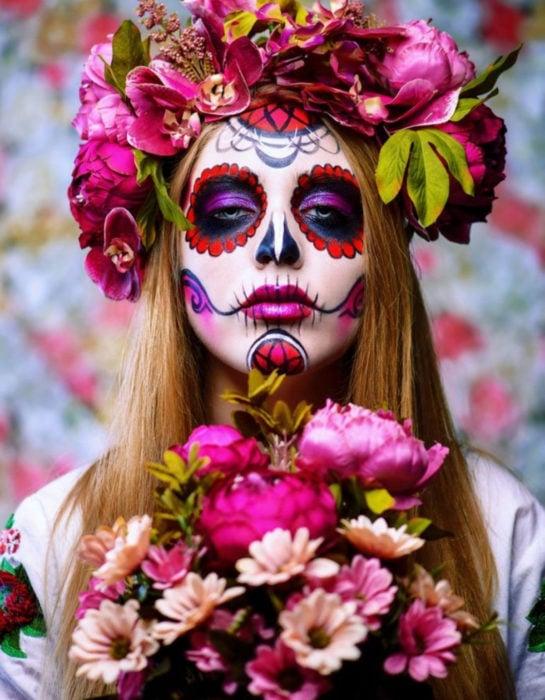 Maquillaje tradicional de Catrina de Día de Muertos color rojo y rosa con corona de flores en le cabeza y ramo