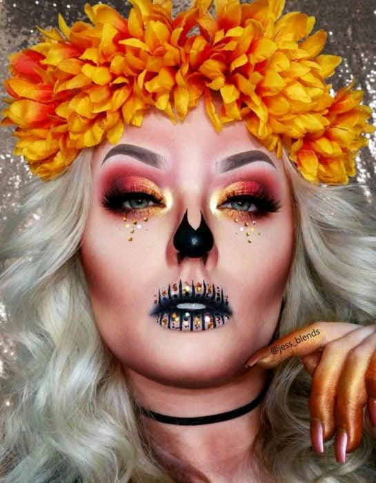 Maquillaje moderno de Catrina de Día de Muertos con flores de cempasúchil en el cabello, ojos con sombras anaranjadas y lentejuelas