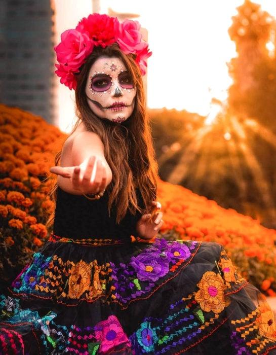 Maquillaje tradicional de Catrina de Día de Muertos con corona de flores en la cabeza y pedrería; chica con falta con flores bordadas en un campo de cempasúchil