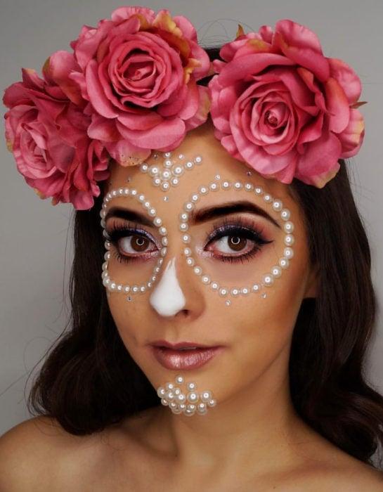 Maquillaje moderno de Catrina de Día de Muertos con corona de rosas en la cabeza y adornos de perlas blancas