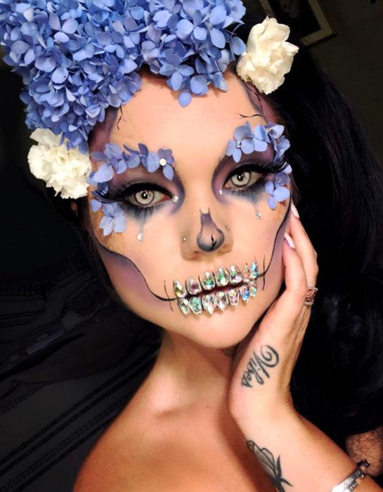 Maquillaje moderno de Catrina de Día de Muertos con flores hortensias en la cabeza y alrededor del ojo